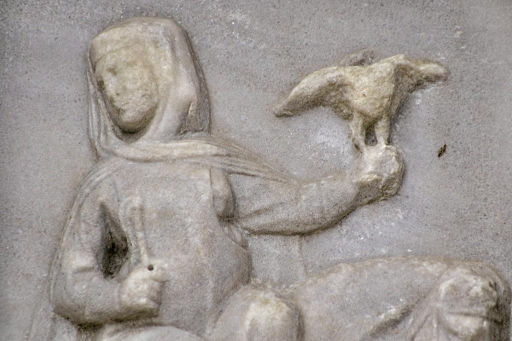 La figura femminile procede a cavallo, mentre regge un frustino e un falcone.