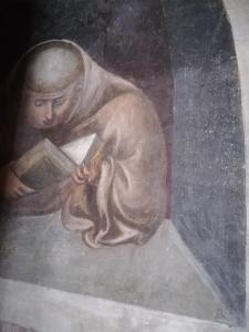 affresco con monaco immerso nella lettura