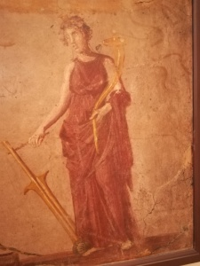 Particolare di affresco pompeiano, conservato al museo archeologico di Napoli, in cui la dea tiene con la destra il timone e con la sinistra la cornucopia